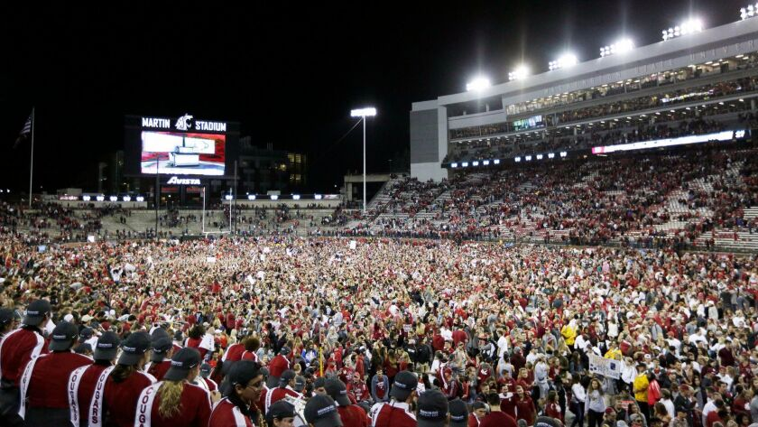 Washington State fans swarm the field after the Cougars' 30-27 victory over USC at Martin Stadium.