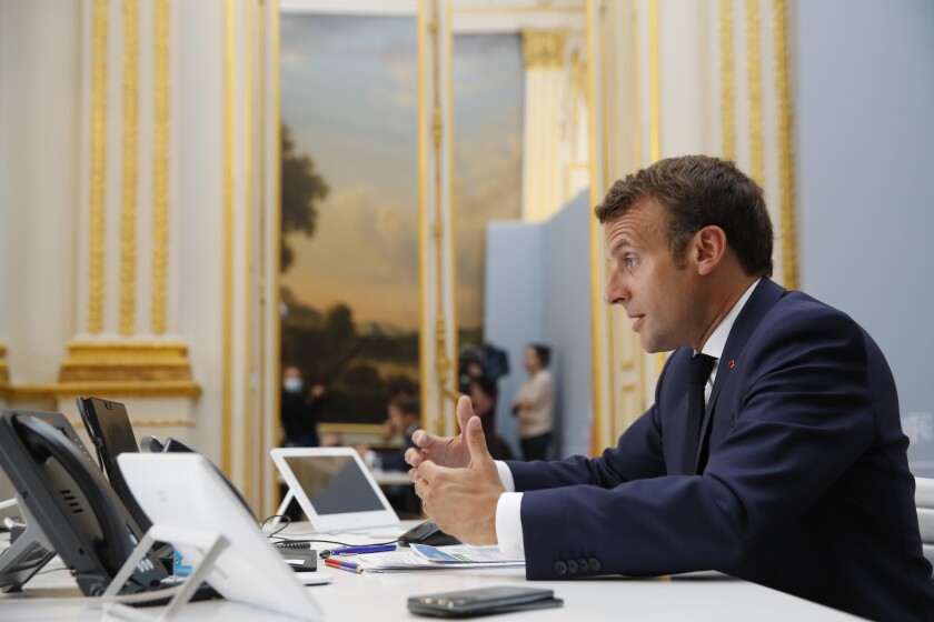 French President Emmanuel Macron speaks with the head of the World Health Organization and other leaders.