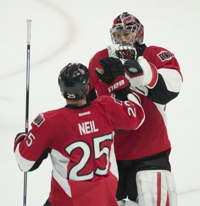 Ottawa Senators' right wing Chris Neil (25) congratulates goalie Craig Anderson following a shootout win against the Buffalo Sabres after of an NHL hockey game, Tuesday, Feb. 16, 2016 in Ottawa, Ontario. The Senators defeated the Sabres 2-1. (Adrian Wyld/The Canadian Press via AP) MANDATORY CREDIT