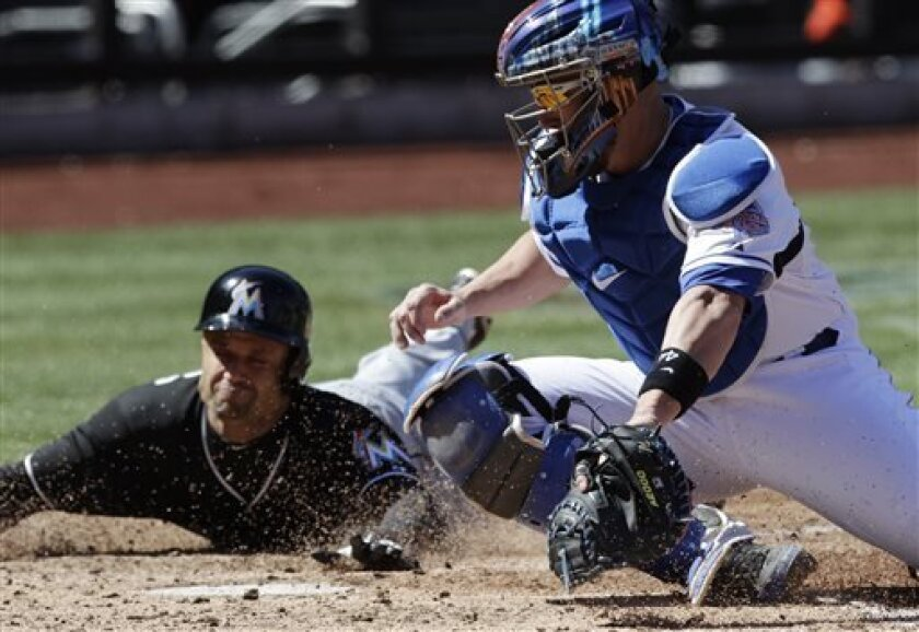 Miami Marlins' Placido Polanco, left, scores from third base as New York Mets catcher John Buck turns to make the late tag in the fifth inning of a baseball game at Citi Field, Saturday, April 6, 2013 in New York. (AP Photo/Mark Lennihan)