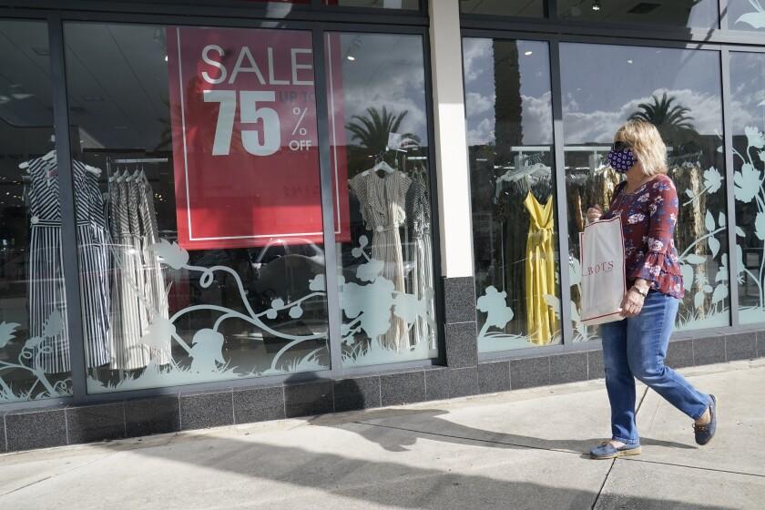 Una compradora pasa por delante de una tienda con un anuncio de descuentos en el escaparte, en Pembroke Pines, Florida.