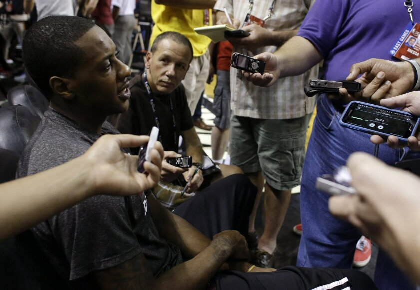 Miami Heat's Mario Chalmers, left, is interviewed during an NBA basketball media availability at the NBA Finals, Wednesday, June 11, 2014, in Miami. Chalmers has a history of coming up big in big moments. Not in these NBA Finals, though. The point guard is in a big-time struggle and his team is in trouble. The San Antonio Spurs lead the Heat 2-1 in the best-of-seven games series. (AP Photo/Lynne Sladky)