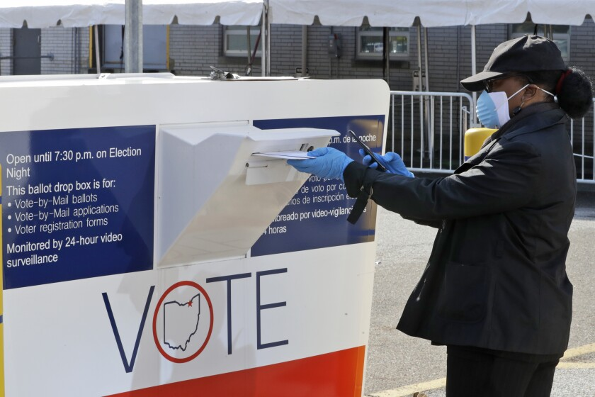 Marcia McCoy drops ballot into a box in Cleveland, Ohio.