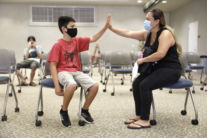 Zuly Gomez, right, congratulates her son Dean, 13, after receiving his first dose of the Pfizer vaccine at El Camino College
