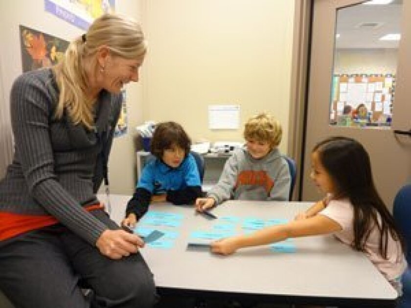 Students at R. Roger Rowe School work with Literacy Support Teacher Katrina Gerace.  These students are doing an exercise which involves expanding their vocabulary by creating compound words.