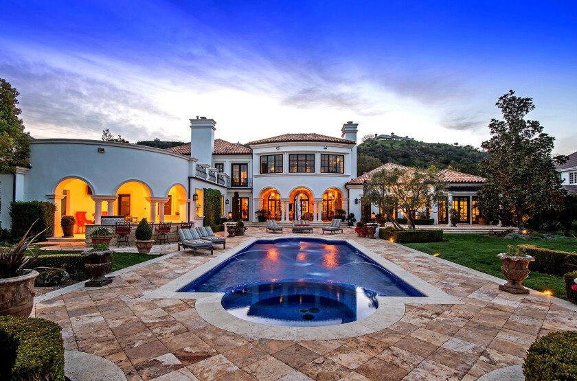 Outside, the 8,380-square-foot house is set off by a custom swimming pool and spa, an outdoor kitchen, a covered patio with a fireplace and a pavilion.