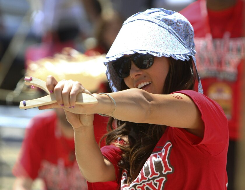 Reality star Maiya Tanaka tries to hit a tin can with a slingshot at one of the 13 checkpoints during the annual Reality Rally in Old Town Temecula Saturday afternoon.