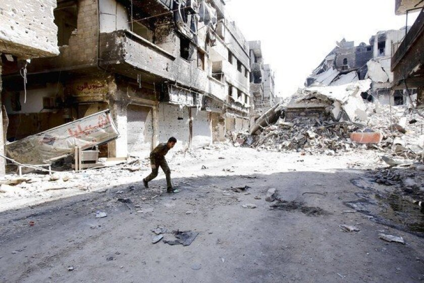 A fighter allied with Syrian President Bashar Assad's government runs through a refugee camp in Damascus last week.