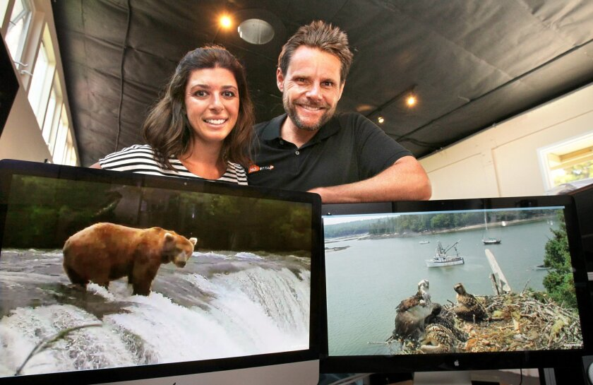 Portrait of Tiffany and Tim Sears with monitors displaying their live web cam views of bears at Brooks Falls at Katmai National Park in Alaska, at left, and ospreys at Hog Island in Bremen, Maine.