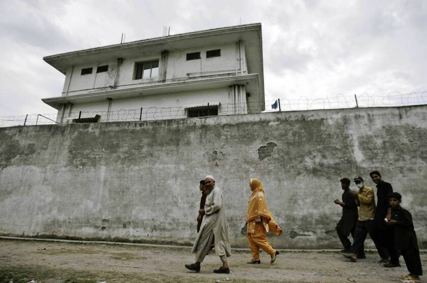Pakistanis walk past the fortress-like residence where Osama bin Laden was living in Abbottabad, Pakistan, when U.S. Navy SEALs killed him during a raid.
