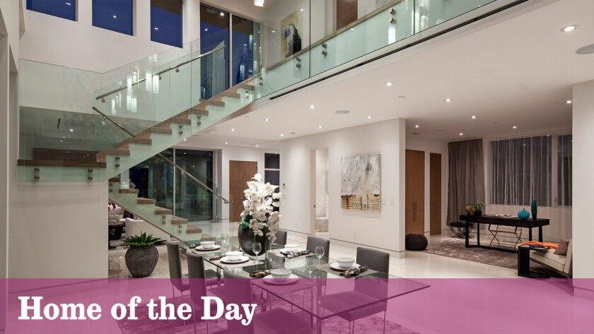 A glass-lined staircase and catwalk are among the features of this newly built contemporary in Beverly Hills.