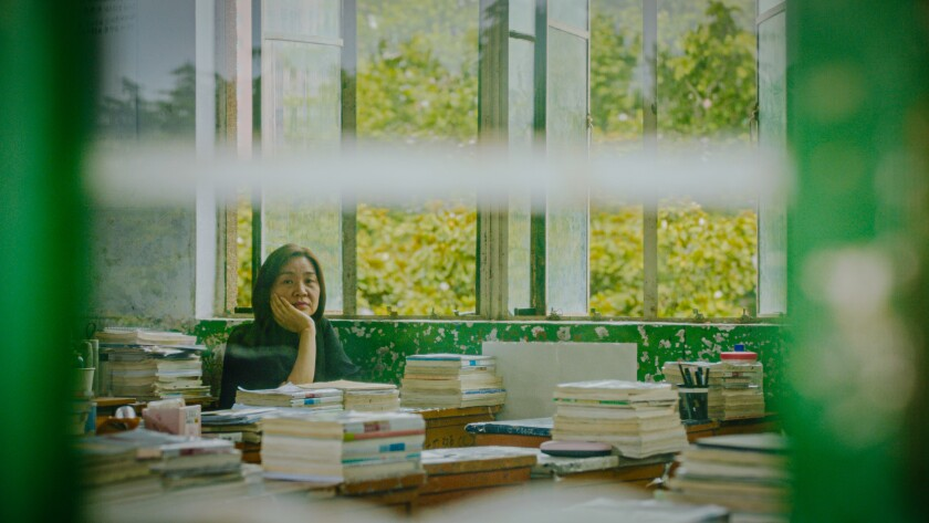 Author Liang Hong sits behind tables stacked with books.