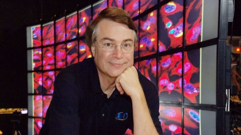 Larry Smarr, director of Calit2 at UC San Diego, in front of a 100-megapixel, 55-panel tiled display showing cancer cells.