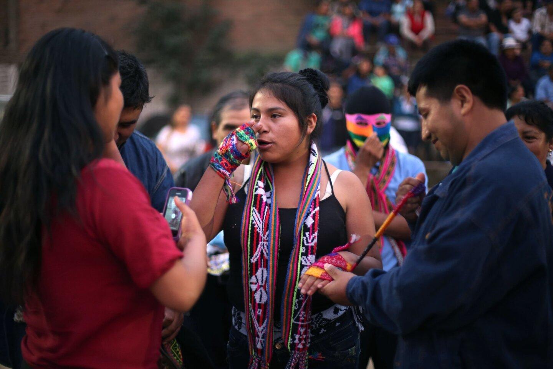 """En esta imagen, Karen Quispe se prepara para luchar contra otra mujer, por deporte, en el """"Takanakuy"""", una lucha ritual, en las afueras de Lima, en Perú, en el día de Navidad. Como las peleas son voluntarias, nadie está obligado a aceptar un desafío. Pero el desafiado puede convocar a un familiar o amigo para que luche en su nombre y su honor no resulte mancillado. Es que negarse a pelear es reconocer la superioridad del contrincante. (Foto AP/Martin Mejia)"""