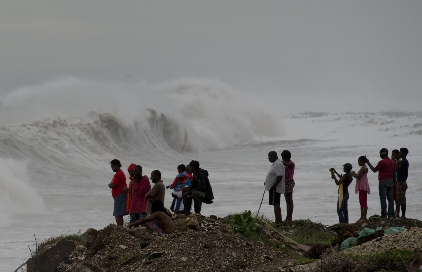 People in Jamaica watch surf generated by Hurricane Matthew on the outskirts of Kingston.