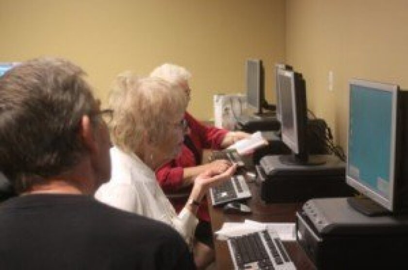 La Jolla Library programs are funded by the Friends and attended by people of all ages. Here, instructor John Ledingham helps Deyon Vanderweele with computer questions during the free, weekly computer lab workshop.