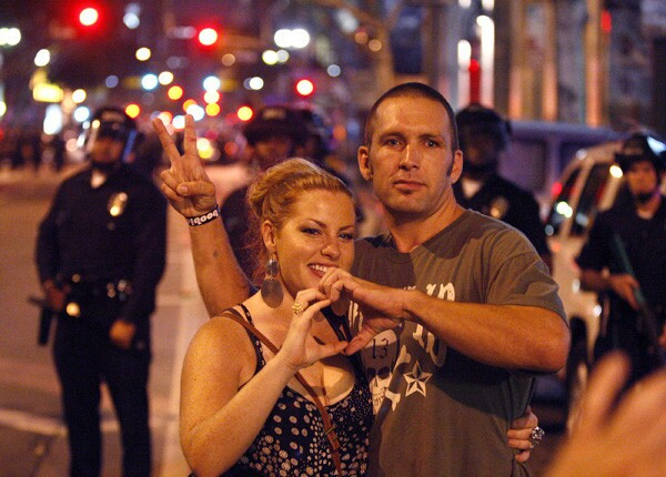 People take photos of themselves Thursday night at the intersection of 5th and Spring Streets as police in riot gear pause from pushing the crowd back.