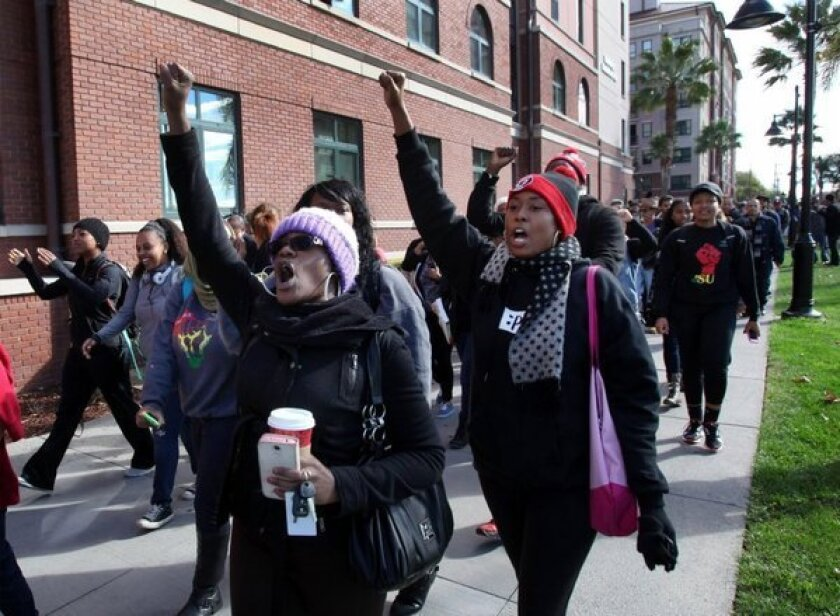 Champagne Ellison, left, a senior at San Jose State University, marches during a protest in November over reported racial hazing of an African American freshman by his dormitory roommates.