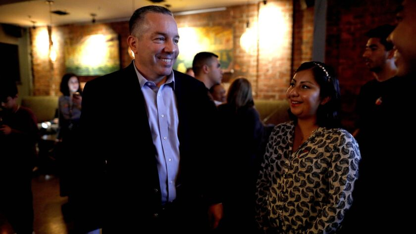 Alex Villanueva, challenger for Los Angeles County sheriff, with Elizabeth Yuson of Los Angeles on election night at Cities Restaurant in Los Angeles.