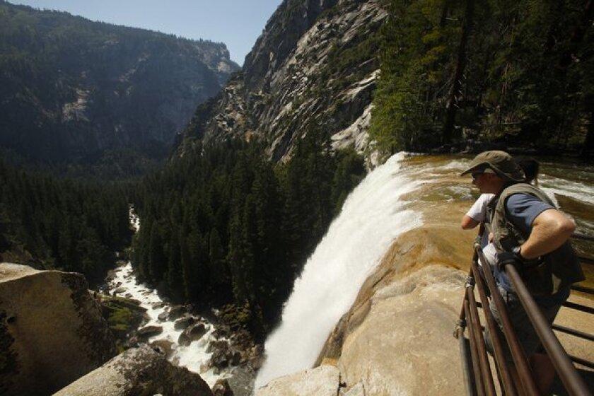 Yosemite National Park visitors look over Vernal Fall .