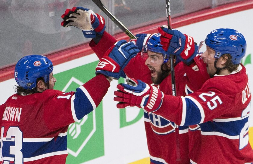 Montreal Canadiens' Lucas Lessio (53) celebrates with teammates Mike Brown (13) and Jacob De La Rose (25) after scoring against the Anaheim Ducks during third period NHL hockey action in Montreal on Tuesday, March 22, 2016. (Graham Hughes/The Canadian Press via AP)