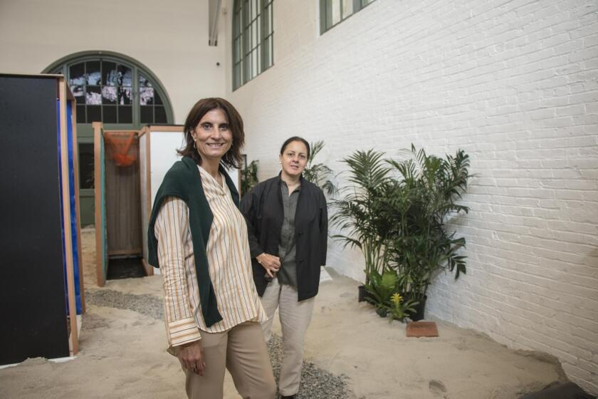At MCASD, executive director Kathryn Kanjo joins Lima Art Museum director Natalia Majluf on the path to 'Tropicalia,' an installation by the groundbreaking Brazilian artist Hélio Oiticica that includes sand, plants, fabric, wooden frames and a live caged parrot.