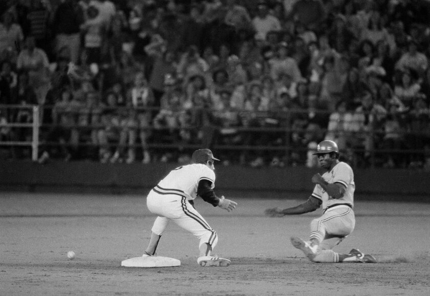 Lou Brock of the St. Louis Cardinals starts his slide into second base as he sets the record for stolen bases at 893, in San Diego, Calf., Aug. 29, 1977. Shortstop Bill Allmon of the San Diego Padres waits for the ball.  (AP Photo/Lennox McLendon)