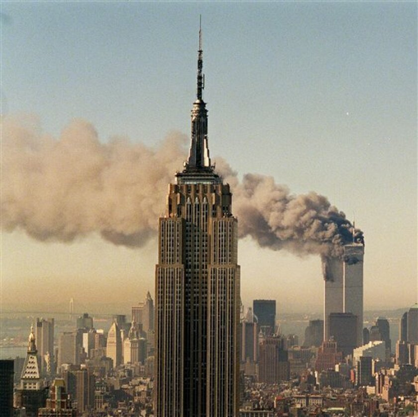 FILE - In this Sept. 11, 2001 file photo, the twin towers of the World Trade Center burn behind the Empire State Building in New York. The Internet Archive, a California-based organization that collects audio, moving images and Web pages for historical purposes, has put together a television news archive of that day's coverage. More than 20 channels were recorded with more than 3,000 hours of television. (AP Photo/Marty Lederhandler, File)