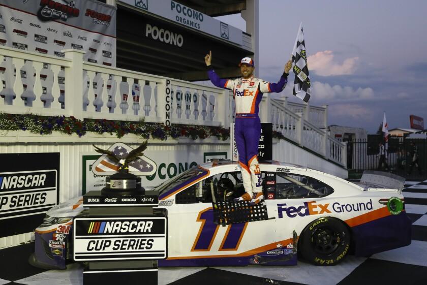 Denny Hamlin celebrates after winning the NASCAR Cup Series auto race at Pocono Raceway.