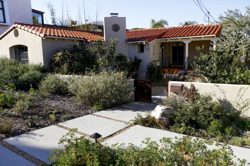 The Olsens' front yard originally featured a semi-circular driveway that took up much of the yard. Today, it features a selection of California native and some nonnative, drought-tolerant plants. Oakley Gardens added California gravel in between the pavers shown here that will allow water to percolate back in to the soil.