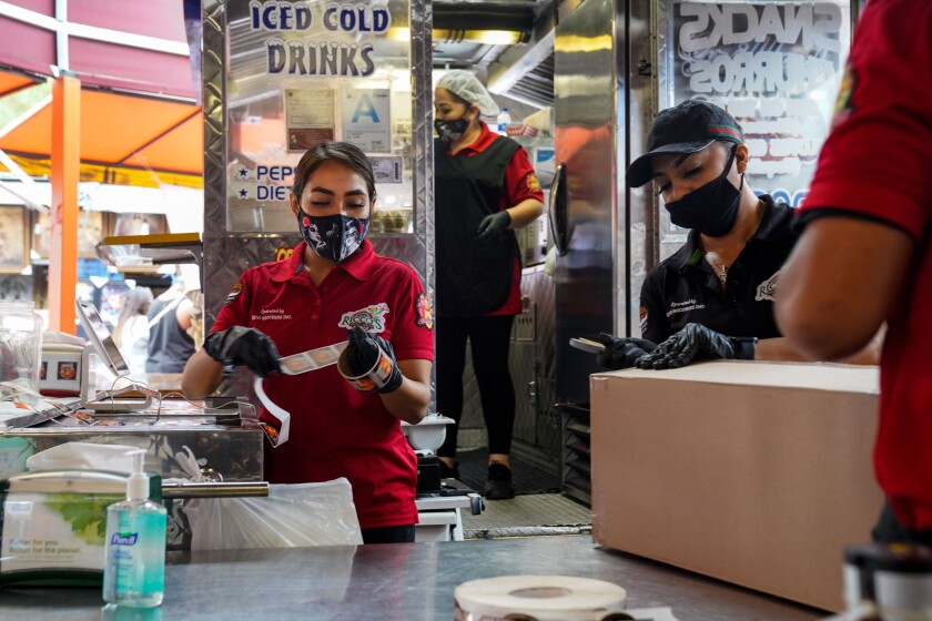 Mask-wearing employees work at a food booth at the Santa Fe Springs Swap Meet on Saturday.