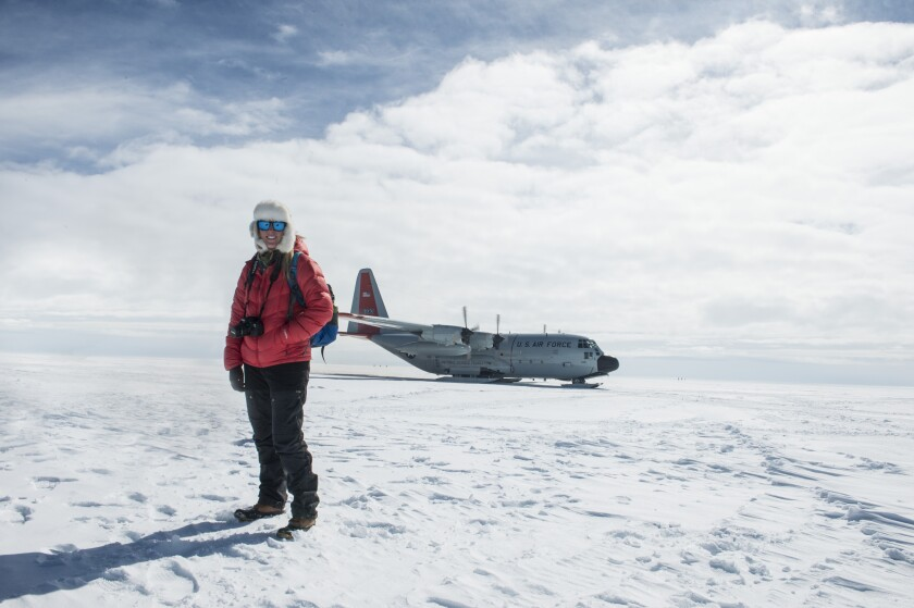 Maggie Shipstead stands before a cargo plane in the snow.