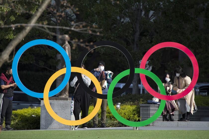 Gente capta fotos de los anillos olímpicos instalados en el Museo Olímpico de Tokio.