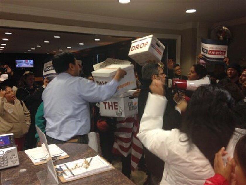 """Jason Chung, director de las iniciativas para la comunidad asiática, recibe de activistas a favor de una reforma migraroria cajas con al menos 33.000 cartas dirigidas al presidente del Partido Republicano Reince Priebus, pidiéndole que """"denuncie a cualquier candidato presidencial que lance ataques racistas a las comunidades inmigrantes como una manera de apelar a los votantes""""."""