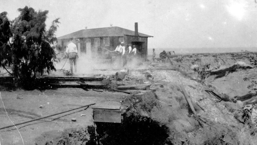 Crews clean up the remains of the original La Jolla Bathhouse, post-fire, in August 1905