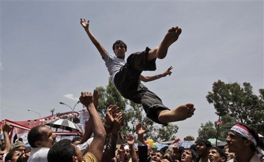 Anti-government protestors reach their hands to catch a protestor after throwing him in to the air as they celebrate President Ali Abdullah Saleh's departure to Saudi Arabia, in Sanaa, Yemen, Sunday, June 5, 2011. Thousands of protesters are dancing and singing in the Yemeni capital Sanaa after the country's authoritarian leader flew to Saudi Arabia to receive medical treatment for wounds he suffered in a rocket attack on his compound. (AP Photo/Hani Mohammed)