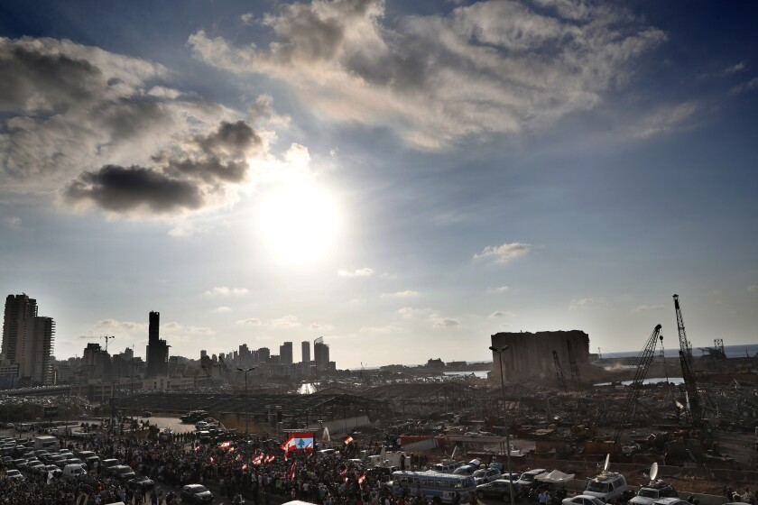 People gather in honor of the victims at the scene of the last week's explosion that killed many and devastated the city, in Beirut, Lebanon, Tuesday, Aug. 11, 2020. (AP Photo/Hussein Malla)