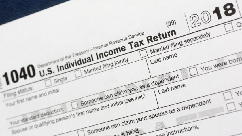 FILE- This July 24, 2018, file photo shows a portion of the 1040 U.S. Individual Income Tax Return f
