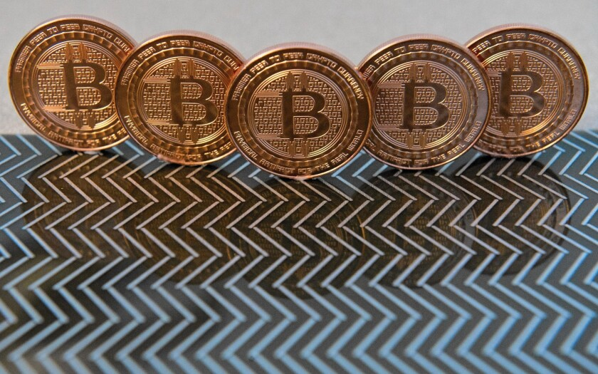 ItBit Trust Co., a New York start-up that allows investors to trade dollars for bitcoins, started operating Thursday under a banking trust charter that it says allows it to function legally in all 50 states. Above, bitcoin medals.