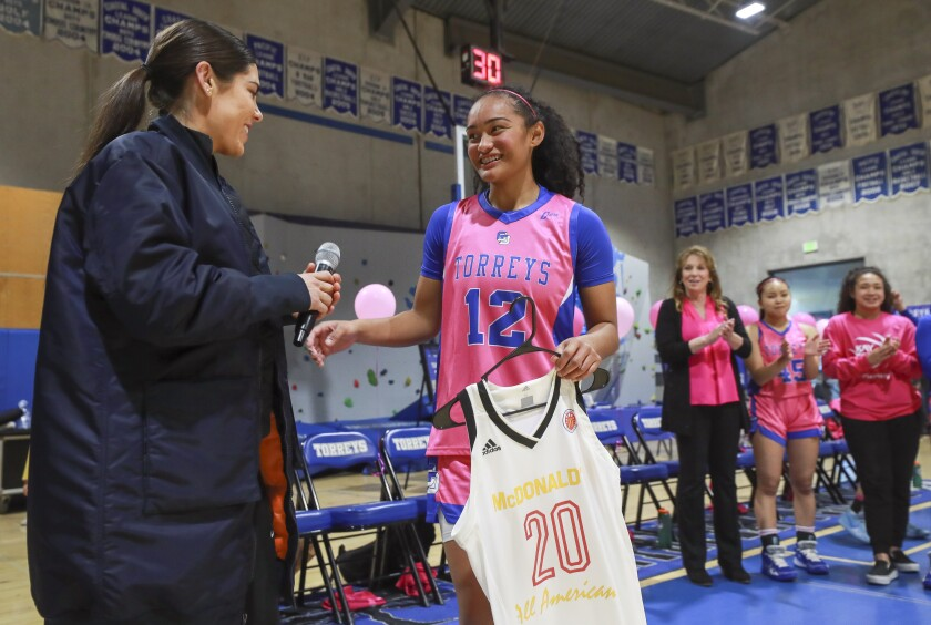 Te-Hina Paopao (right) receives her McDonald's All-American jersey from LJ Country Day alum Kelsey Plum.