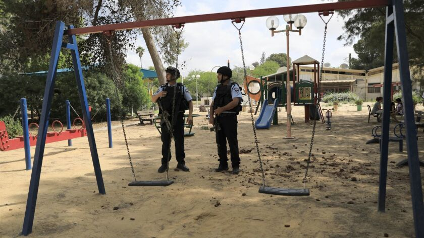 Israeli police officers guard a playground in a kibbutz near the Israel and Gaza border, Tuesday, Ma