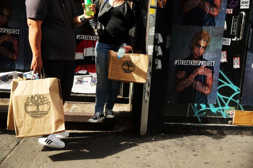 People hold shopping bags along Broadway in New York City on Oct. 15.