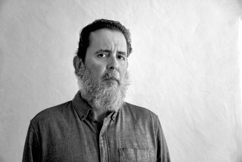A black-and-white portrait of a bearded man in a button-down shirt