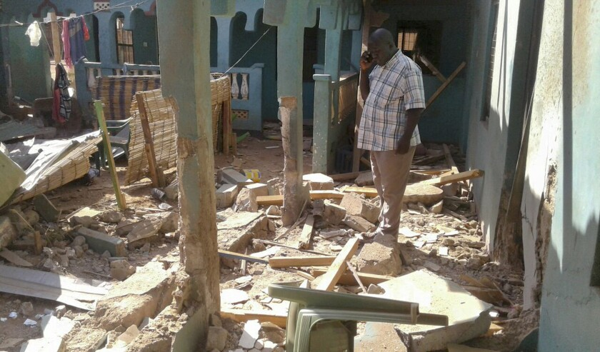 A man stands amid the debris at the scene of an attack in the town of Mandera, Kenya, near the border with Somalia, Tuesday, Oct. 25, 2016.