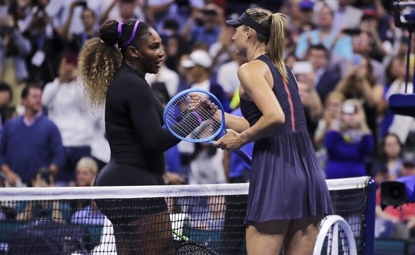 Serena Williams, left, shakes hands with Maria Sharapova after their first-round match at the U.S. Open on Monday.
