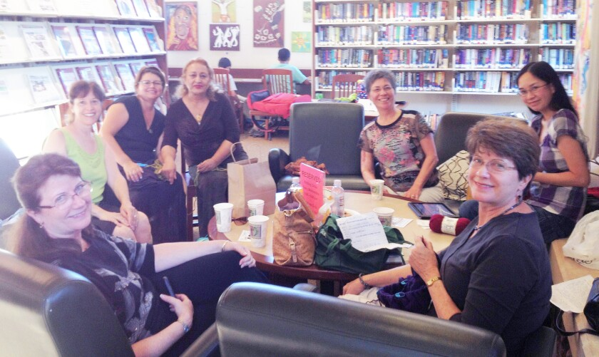 Some Chicks with Sticks Knitting Club members meeting near the 4S Ranch Library fireplace before the COVID-19 pandemic.