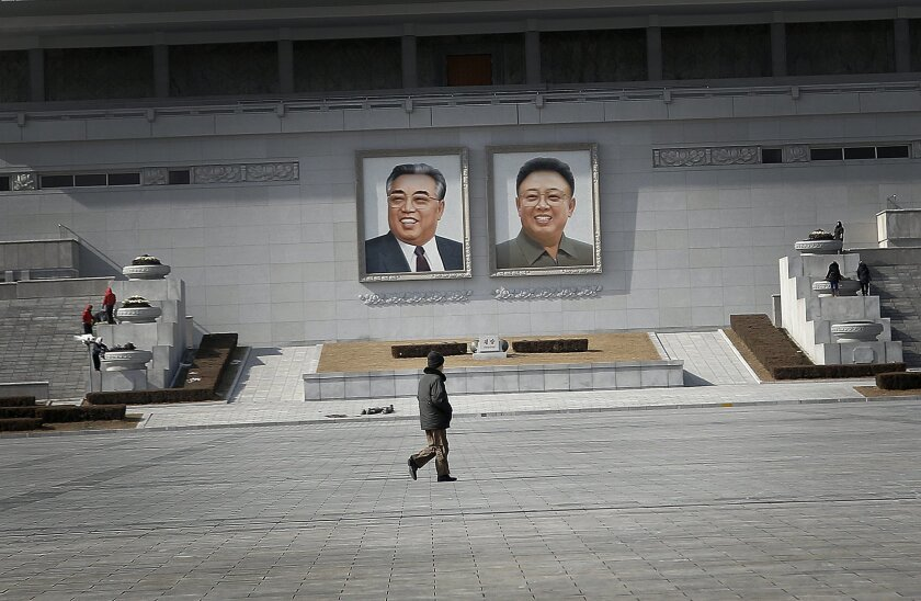 A man walks past portraits of the late North Korean leaders Kim Il Sung and Kim Jong Il, at the Kim Il Sung Square on Sunday, Feb. 14, 2016, in Pyongyang, North Korea. North Korea launched a rocket Feb. 7, carrying what it said was an Earth observation satellite into space. The U.N. Security Counci
