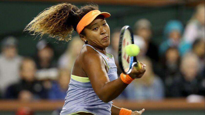 Naomi Osaka returns a shot to Simona Halep during their semifinal match Friday night.