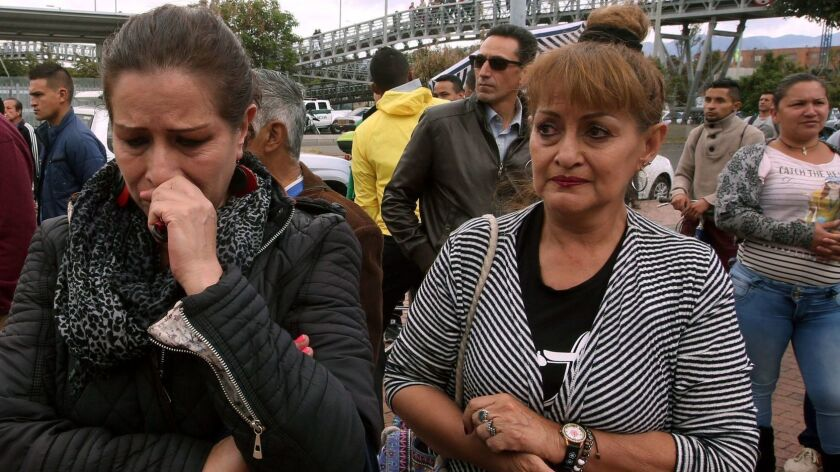People wait for information about their relatives near a police academy car bomb explosion in Bogota, Colombia, on Thursday.