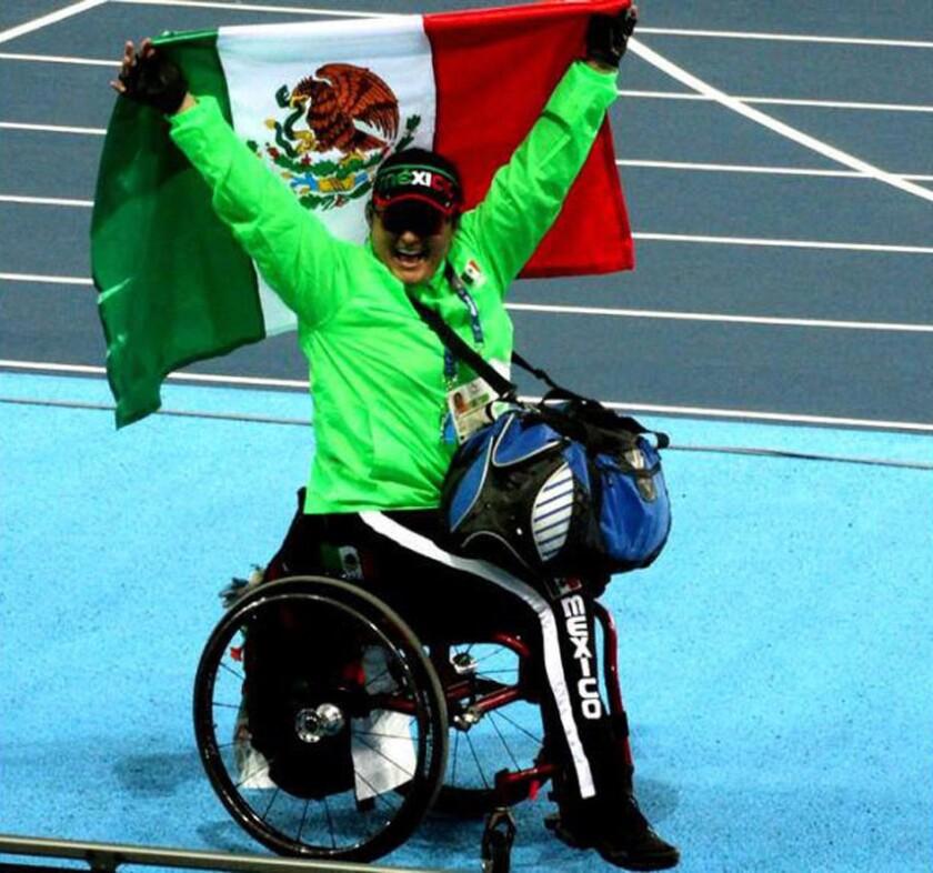 Ángeles Ortíz celebra con la bandera de México tras ganar medalla de oro en la prueba de Lanzamiento de bala.
